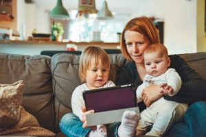 Mom and children on couch with ipad